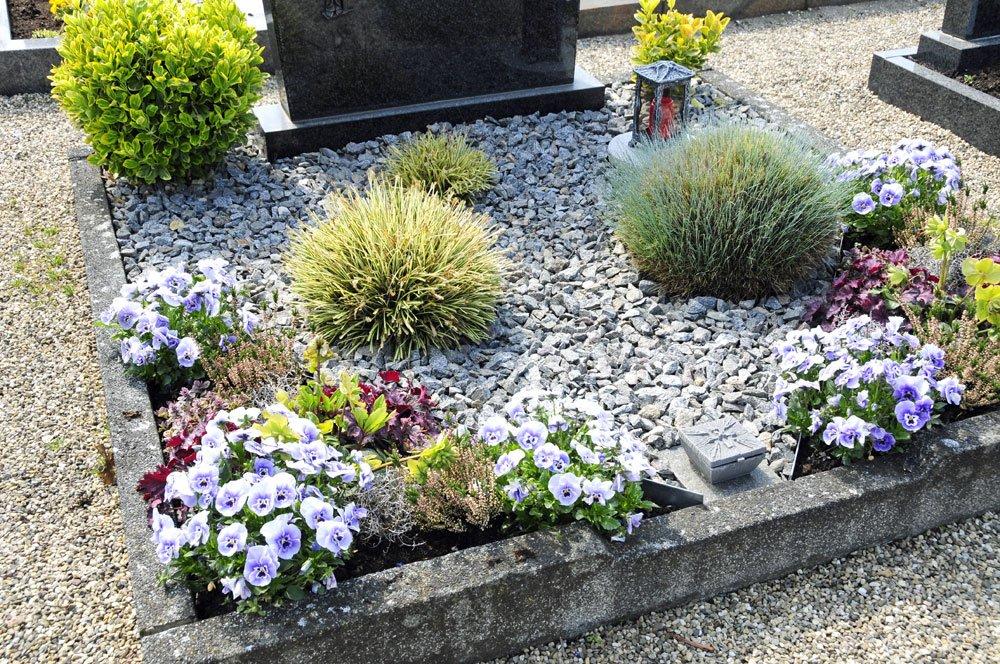 Grab mit Kies und Pflanzen