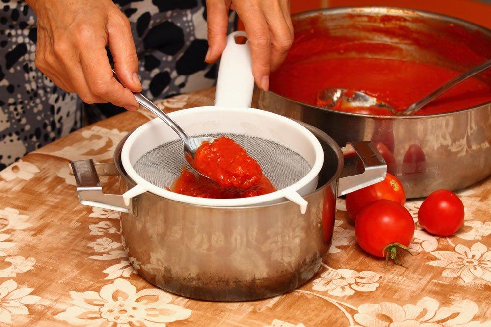 Tomaten durch ein Sieb passieren